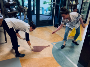 Twee assistentes ruimen diarree op van de vloer in een dierenkliniek